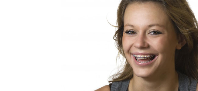 A young girl with braces smiles to show that we offer traditional braces and Invisalign at our Naperville practice.