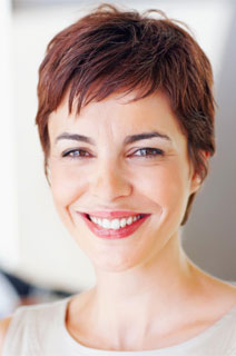 A smiling woman illustrates how our Naperville dentist uses Periodontics to help with overall health.