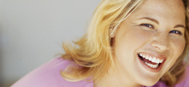 A smiling woman shows how our Cosmetic Dentist in Naperville can beautify your smile.