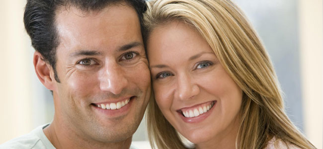 A smiling couple shows how Porcelain Veneers from our Naperville dentist can give you the smile of your dreams.