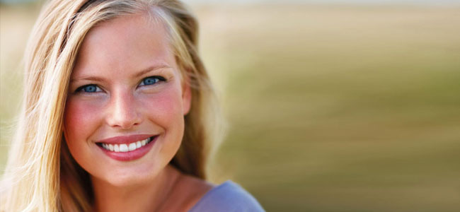 A woman smiles to show how Teeth Whitening from our Naperville dentist can brighten your smile.