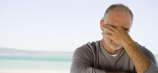 A man holding his head illustrates how TMJ pain can effect our Naperville patients. See Dr. Lakota for relief from TMJ pain.