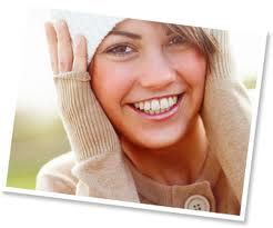 A smiling woman shows how proper dental hygiene can keep your smile looking great.